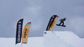 El Snowboarder en salto uniforme del trampolín, hace tirones en aire MONTAÑAS NEVADO Paisaje extremo almacen de video