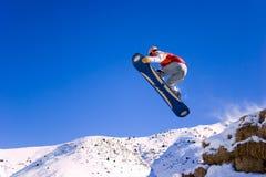El Snowboarder está en salto Imagen de archivo libre de regalías
