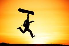 El snowboarder feliz salta el esquí de la puesta del sol Imágenes de archivo libres de regalías