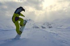 El Snowboarder hace los aumentos del truco el frente del tablero imagen de archivo libre de regalías