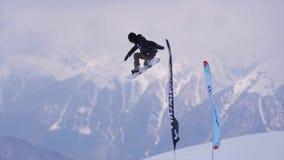El Snowboarder hace salto de altura extremo en el aire del trampolín en montañas de la nieve Banderas de la competencia metrajes
