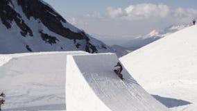 El Snowboarder hace salto extremo en el trampolín truco Día asoleado Montañas metrajes