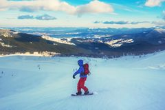 El Snowboarder monta abajo de la cuesta de montaña en la estación de esquí Fotos de archivo libres de regalías