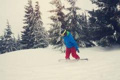 El Snowboarder monta abajo en las montañas, en las condiciones duras Fotografía de archivo libre de regalías
