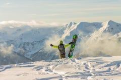 El Snowboarder parasitario se está colocando en las montañas nevosas en invierno debajo de las nubes foto de archivo libre de regalías