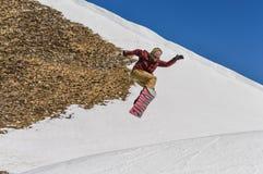 El Snowboarder que disfruta de funcionamientos y los saltos en el ` s de la primavera duran nieve Fotografía de archivo libre de regalías