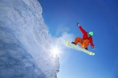El Snowboarder que salta contra el cielo azul fotografía de archivo