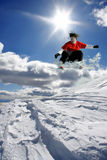el snowboarder que salta contra el cielo azul Imagen de archivo libre de regalías