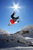 El Snowboarder que salta contra el cielo azul Imagen de archivo