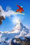 El Snowboarder que salta contra el pico de Cervino en Suiza Fotos de archivo