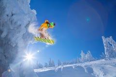 El Snowboarder que salta contra puesta del sol imagenes de archivo