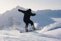 El Snowboarder que salta de cuesta en el fondo de montañas Foto de archivo libre de regalías