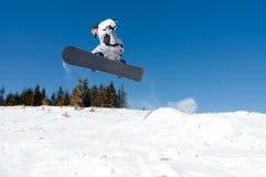 El Snowboarder que salta del golpeador de la nieve Foto de archivo