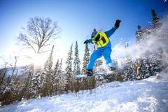 El Snowboarder que salta del trampolín contra el cielo Foto de archivo libre de regalías