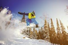 El Snowboarder que salta del trampolín contra el cielo Imagen de archivo
