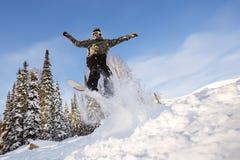 El Snowboarder que salta del trampolín contra el cielo Fotos de archivo