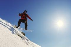 El Snowboarder que salta del trampolín contra el cielo Fotos de archivo libres de regalías