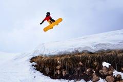 El Snowboarder que salta del trampolín en una colina nevosa con la hierba Foto de archivo libre de regalías