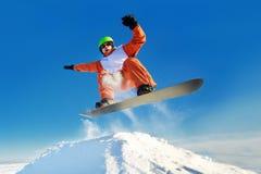 El Snowboarder que salta el cielo azul en fondo Fotos de archivo