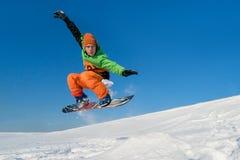 El Snowboarder que salta el cielo azul en fondo Fotografía de archivo