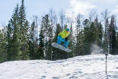 El Snowboarder que salta en las montañas en un fondo del bosque foto de archivo