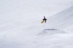 El Snowboarder que salta en parque de la nieve en la estación de esquí el día de invierno del sol Fotos de archivo libres de regalías