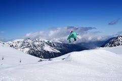 El Snowboarder que salta en parque de la nieve en la montaña del invierno en sunn agradable Imagen de archivo libre de regalías