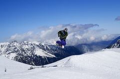 El Snowboarder que salta en parque del terreno en la montaña de la nieve en los wi soleados Imagen de archivo libre de regalías