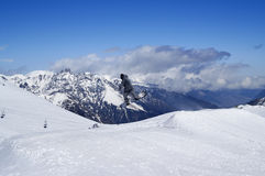 El Snowboarder que salta en parque del terreno en la montaña de la nieve en wint del sol Imagen de archivo