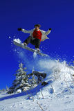 El Snowboarder que salta sobre el árbol Imágenes de archivo libres de regalías