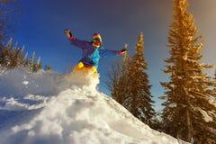 El Snowboarder que salta a través del aire con el cielo azul profundo en fondo Imágenes de archivo libres de regalías