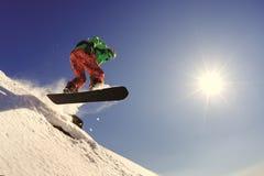 El snowboarder salta del trampolín contra el cielo azul Imagenes de archivo