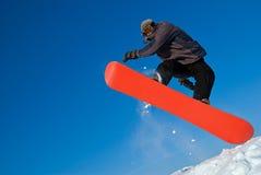 El Snowboarder salta en el aire, vuelo de la nieve Foto de archivo