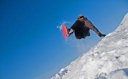 El Snowboarder salta en el aire, vuelo de la nieve Imagen de archivo