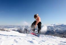 El Snowboarder salta para arriba en la montaña Imagenes de archivo