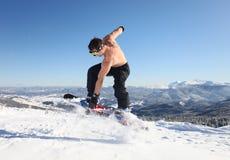El Snowboarder salta para arriba en la tapa de la montaña Imagen de archivo libre de regalías