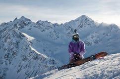 El Snowboarder se está sentando en cuestas de montaña de un volcán extinto Elbrus imagen de archivo