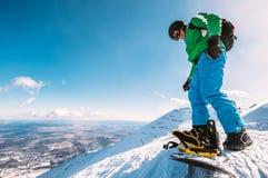 El Snowboarder se prepara para esquiar abajo desde arriba de la colina de la nieve Imagen de archivo libre de regalías