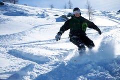 El snowboarder va para un mecanismo impulsor en montañas Fotos de archivo libres de regalías