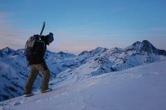 El snowboarder valiente con la mochila y la snowboard suben en la montaña nevosa en la tarde Imágenes de archivo libres de regalías