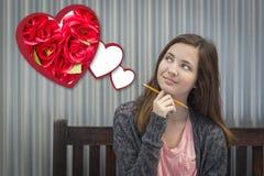 El soñar despierto adolescente de la muchacha de Valentine Hearts con las rosas rojas Imagenes de archivo