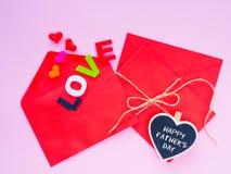 El sobre abierto y muchos sentían corazones colorido de corazones con el texto del AMOR en fondo rosado Foto de archivo