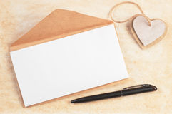 El sobre con la hoja en blanco adornó corazones y la pluma de la cartulina en viejo fondo de papel con el espacio para el texto Fotos de archivo