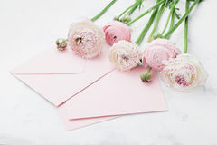 El sobre o la letra, la tarjeta de papel y el ranúnculo rosado florece en la tabla blanca para saludar el día de la madre o de la imagen de archivo