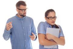 El socio abusivo del trabajo asusta al compañero de trabajo femenino Imagenes de archivo