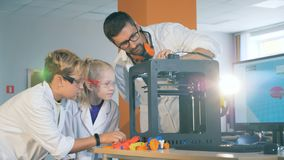 El socio del laboratorio está demostrando proceso de trabajo de una impresora 3D a los niños almacen de metraje de vídeo