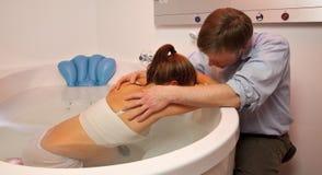 El socio detiene a la esposa embarazada en piscina de la natalidad Imagen de archivo libre de regalías