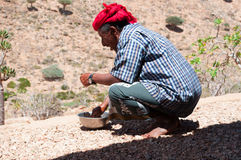 El Socotra, Yemen, un hombre se lava las manos en un cuenco en el bosque de Dragon Blood Trees en la meseta de Homhil Foto de archivo