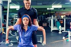 El sofá masculino entrena a la mujer en la ropa de deportes que levanta algunos pesos Imagen de archivo libre de regalías