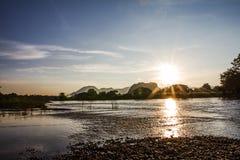 El sol brilla a través del río por la tarde como el fondo Foto de archivo libre de regalías